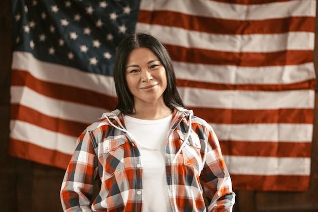 Uśmiechnięta azjatycka kobieta na amerykańskiej flaga