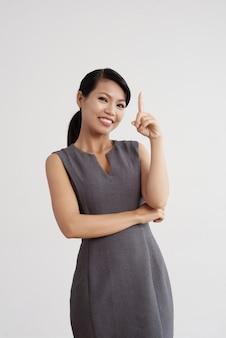 Uśmiechnięta azjatycka kobieta pozuje w studiu i trzyma jeden palec up