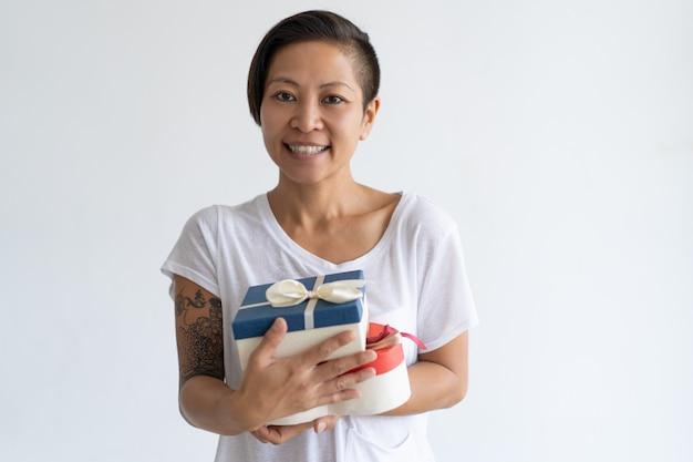 Uśmiechnięta azjatycka kobieta trzyma dwa prezenta pudełka