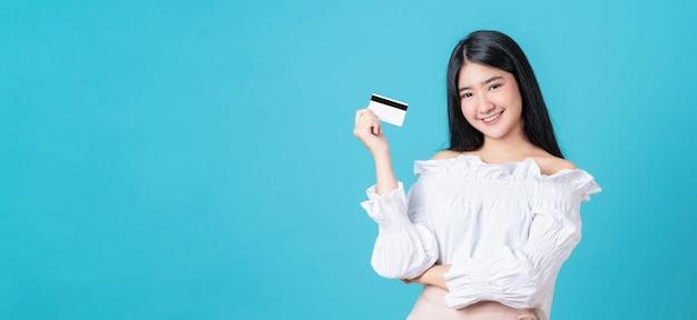 Uśmiechnięta azjatycka kobieta trzyma kredytowej karty zapłatę z krzyżować rękami przeciw i patrzeje naprzód na błękitnym tle z kopii przestrzenią.
