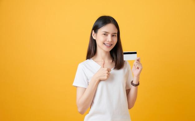 Uśmiechnięta azjatycka kobieta trzyma kredytowej karty zapłatę z przedstawieniami jak znak i patrzeje naprzód na żółtym tle z kopii przestrzenią.