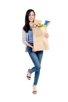 Uśmiechnięta azjatycka kobieta trzyma papierowego torba na zakupy warzywa i sklepy spożywczy pełno