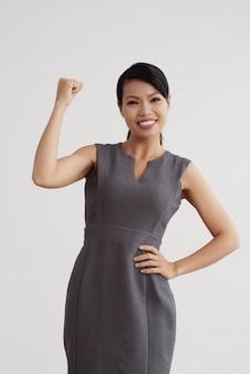 Uśmiechnięta azjatycka kobieta w biznes sukni pozuje w studiu i napina jej rękę