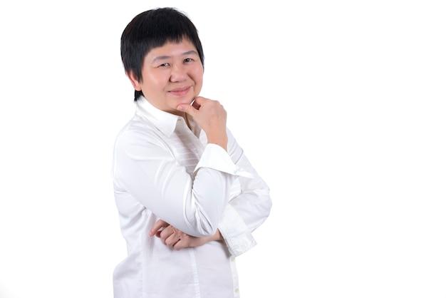Uśmiechnięta azjatycka kobieta w średnim wieku w białej koszuli dotyka twarzy na białym tle
