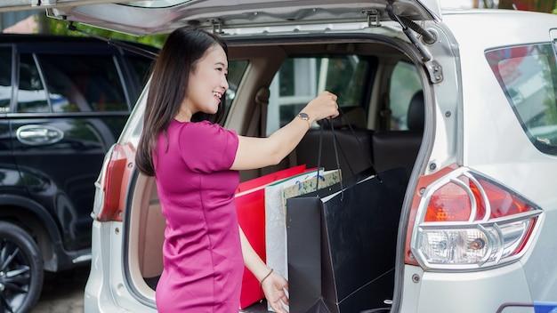 Uśmiechnięta azjatycka kobieta wkłada torby na zakupy do bagażnika samochodu