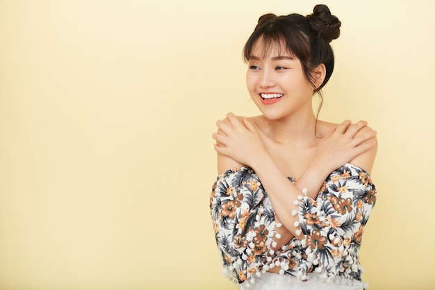 Uśmiechnięta azjatycka kobieta z rękami na ramionach pozuje i patrzeje na boku
