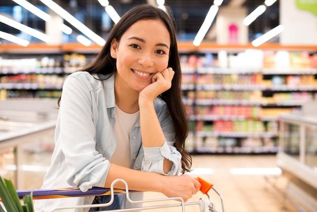 Uśmiechnięta azjatycka kobieta z wózek na zakupy przy supermarketem