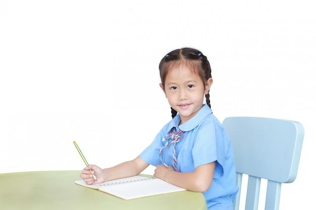 Uśmiechnięta azjatycka mała dziewczynka w mundurka szkolnego writing na notatniku przy biurkiem odizolowywającym. koncepcja uczennica i edukacji.