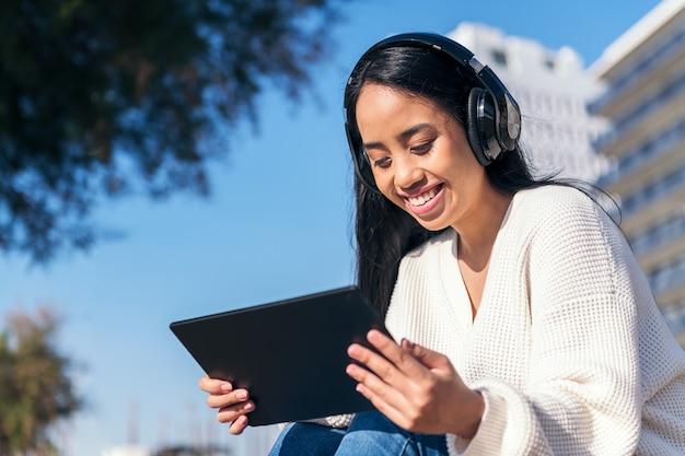 Uśmiechnięta azjatycka młoda kobieta ze słuchawkami ogląda filmy na swoim tablecie, siedząc na zewnątrz