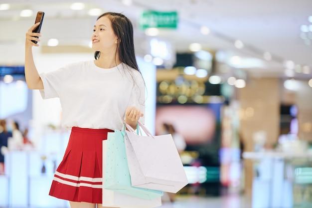 Uśmiechnięta azjatycka nastolatka z torbami na zakupy robi selfie w centrum handlowym