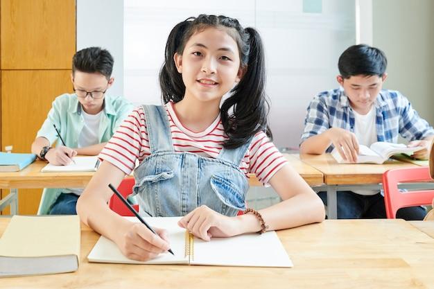 Uśmiechnięta azjatycka uczennica pisze esej w podręczniku podczas zajęć z języka angielskiego