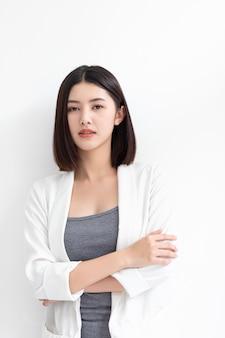 Uśmiechnięta azjatykcia biznesowej kobiety pozycja i patrzeć kamerę
