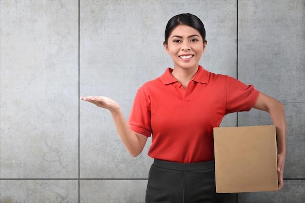 Uśmiechnięta azjatykcia doręczeniowa kobieta z pakuneczkiem