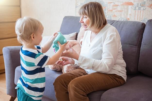 Uśmiechnięta babcia i wnuk bawią się w salonie miękkimi zabawkami. koncepcja życia prawdziwych ludzi. szczęśliwy dzień babci i dziadka