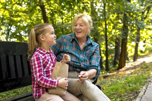 Uśmiechnięta babcia siedzi na ławce z wnuczką w parku