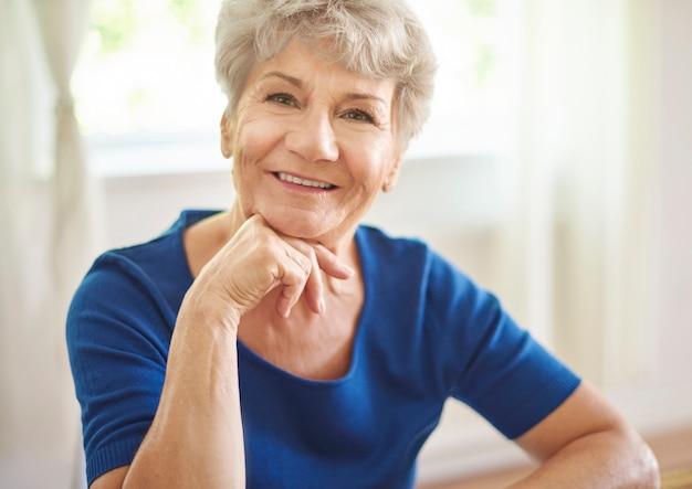 Uśmiechnięta babcia siedzi przy stole
