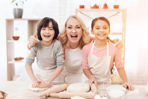 Uśmiechnięta babcia z dzieciakami patrzeje kamerę