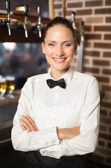 Uśmiechnięta barmanka z rękami skrzyżowanymi