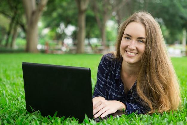 Uśmiechnięta beautiful girl pracy na laptopie na trawie