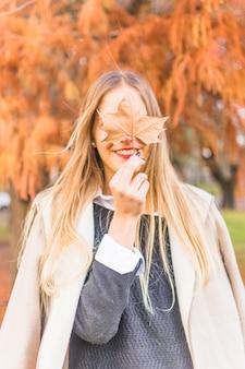 Uśmiechnięta beztwarzowa kobieta z jesień lea