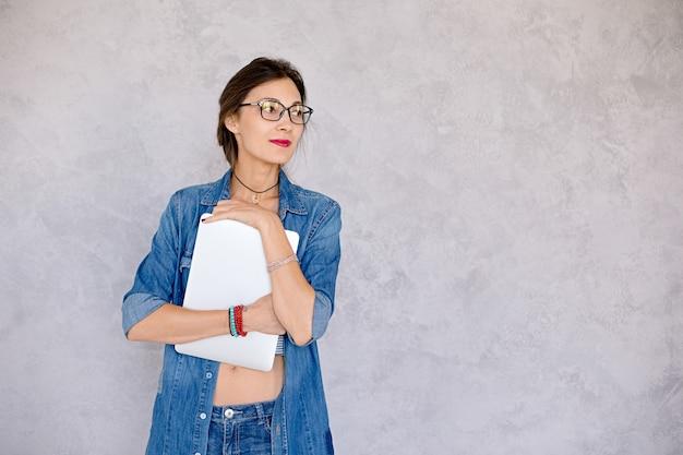 Uśmiechnięta biurowa kobieta obejmuje laptop