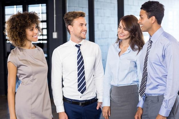 Uśmiechnięta biznes drużyna stoi wpólnie i oddziała wzajemnie w biurze
