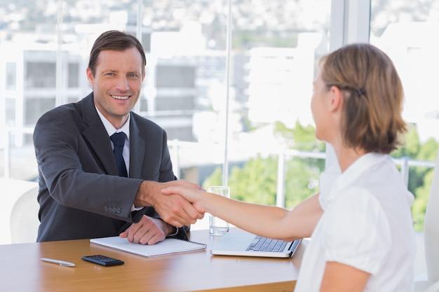 Uśmiechnięta biznesmena chwiania ręka kandydat do pracy
