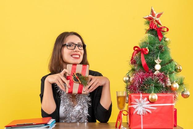 Uśmiechnięta biznesowa dama w garniturze w okularach, trzymając jej prezent i siedząc przy stole z drzewem xsmas na nim w biurze