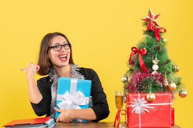 Uśmiechnięta biznesowa dama w garniturze w okularach trzymająca prezent wskazujący za i siedząca przy stole z choinką w biurze