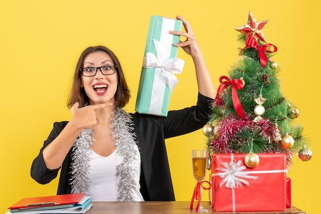 Uśmiechnięta biznesowa dama w garniturze w okularach, wskazując niespodziewanie jej prezent i siedząca przy stole z drzewem xsmas w biurze
