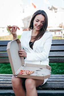 Uśmiechnięta biznesowa dziewczyna jedzenie pizzy na ulicy