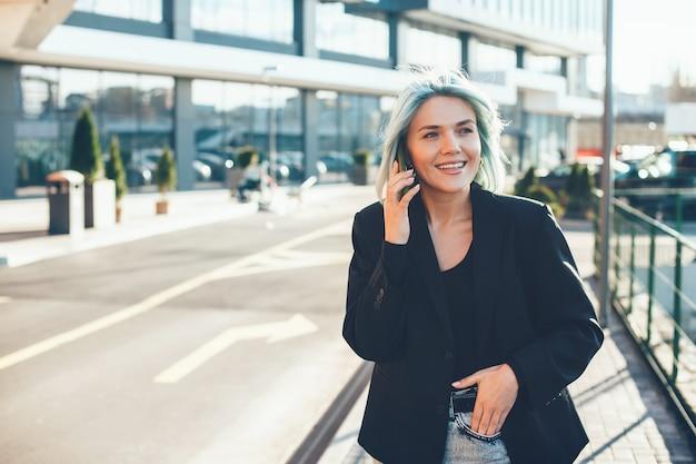 Uśmiechnięta biznesowa kobieta o niebieskich włosach prowadzi rozmowę telefoniczną podczas spaceru na zewnątrz