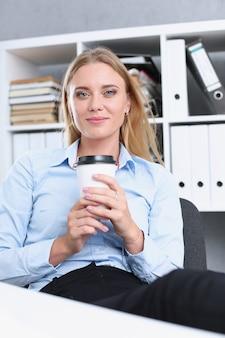 Uśmiechnięta biznesowa kobieta pijąca kawę z papierowego kubka