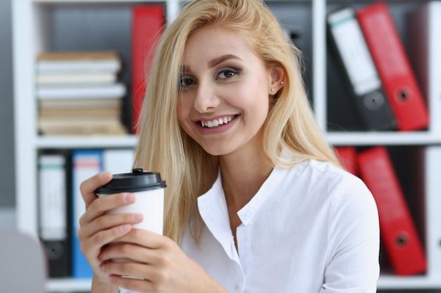Uśmiechnięta biznesowa kobieta pije kawę od papierowej filiżanki w biurowym portrecie patrzeje w kamery mienie w jej ręce i odpoczywa podczas przerwy.