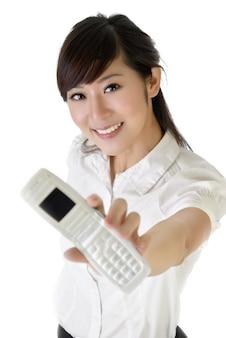 Uśmiechnięta biznesowa kobieta pokazuje telefon komórkowy przy tobie na białej ścianie.