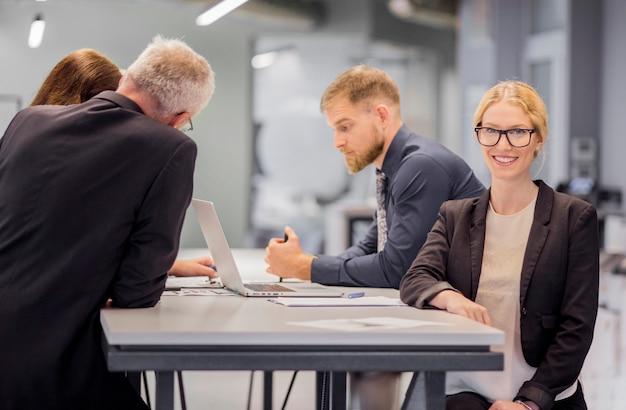 Uśmiechnięta biznesowa kobieta przed jej kolegą pracuje przy miejscem pracy