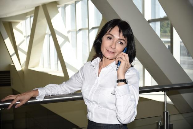 Uśmiechnięta biznesowa kobieta rozmawia przez telefon