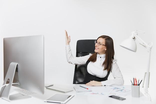 Uśmiechnięta biznesowa kobieta siedząca przy biurku, pracująca przy komputerze z dokumentami w jasnym biurze