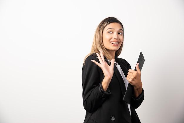 Uśmiechnięta biznesowa kobieta trzyma schowek.