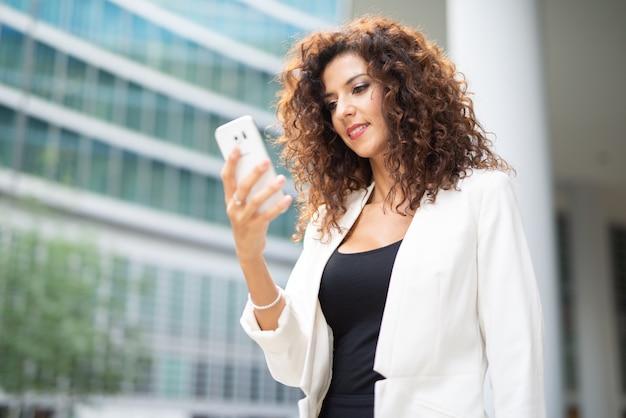 Uśmiechnięta biznesowa kobieta używa jej mobilnego telefon komórkowego podczas gdy chodzący outdoors