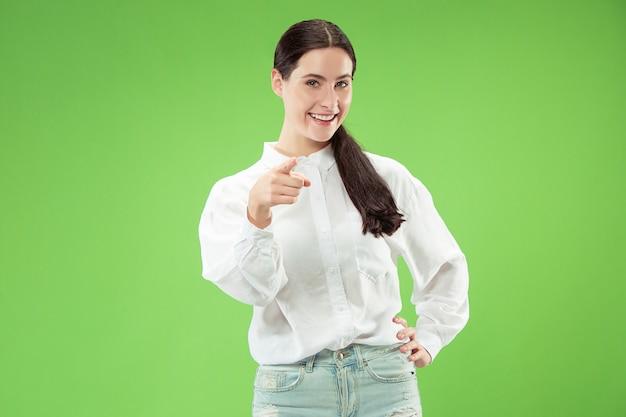 Uśmiechnięta biznesowa kobieta wskazać ci, chce cię, portret zbliżenie w połowie długości na zielonym tle studia.