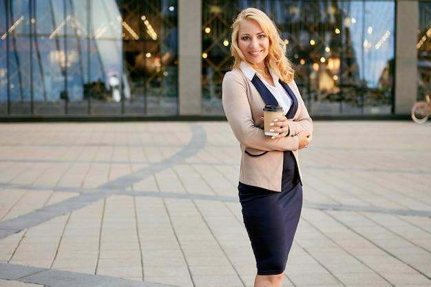 Uśmiechnięta biznesowa kobieta z kawą w papierowym kubku stoi w pobliżu biurowca