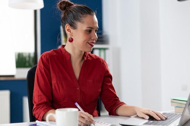 Uśmiechnięta bizneswoman czyta dane z ekranu laptopa laptop