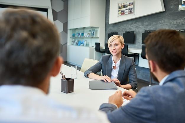 Uśmiechnięta bizneswoman rozmawia z partnerami