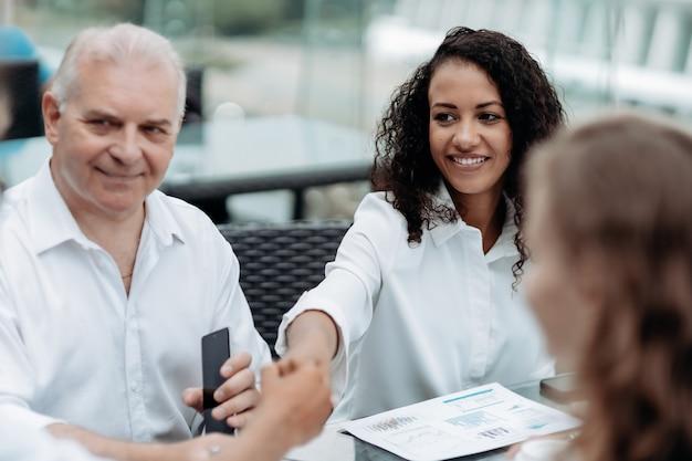 Uśmiechnięta bizneswoman ściska rękę swoich kolegów