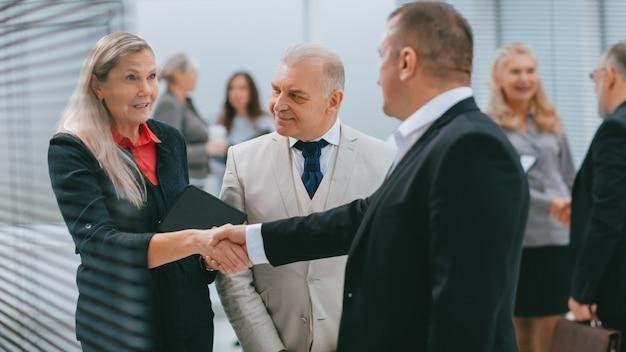 Uśmiechnięta bizneswoman spotykająca się z kolegami z uściskiem dłoni