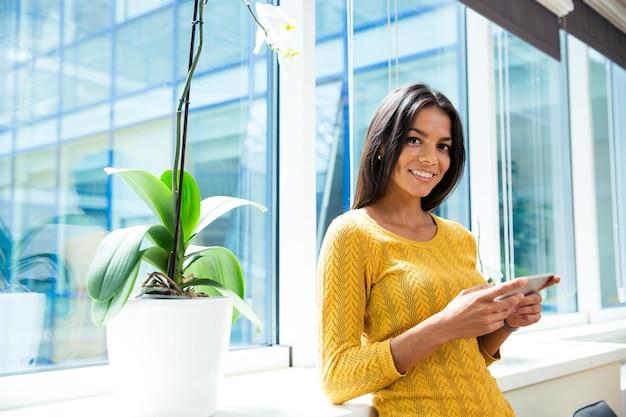 Uśmiechnięta bizneswoman używająca smartfona w biurze w pobliżu okna