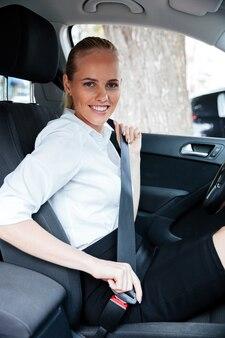 Uśmiechnięta blond biznesowa kobieta siedzi w samochodzie i zakłada pas bezpieczeństwa