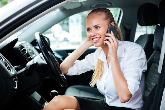 Uśmiechnięta blond bizneswoman prowadząca samochód i rozmawiająca przez telefon komórkowy