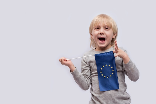 Uśmiechnięta blond chłopiec trzyma ue flaga w ręce na biel przestrzeni. koncepcja wyszkolona w europie